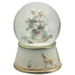Boule Père Noël et garçon sur cheval à bascule