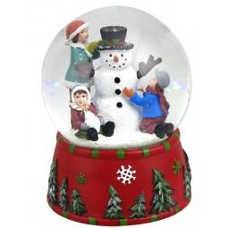 Boule enfants faisant un bonhomme de neige avec neige et paillettes